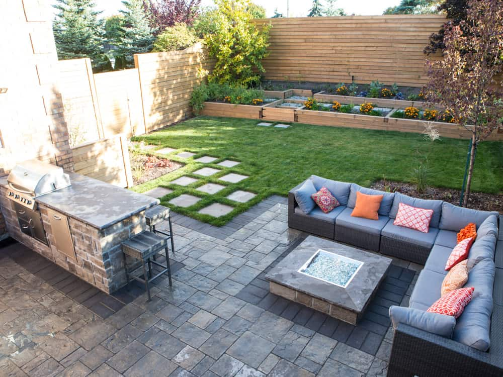 Backyard with couch surrounding a fireplace, with a stone barbecue.
