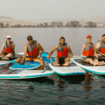 About us photo - our team (and their families), sitting about on paddle boards.
