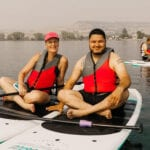 Laureen and her partner smile while sitting on paddle boards