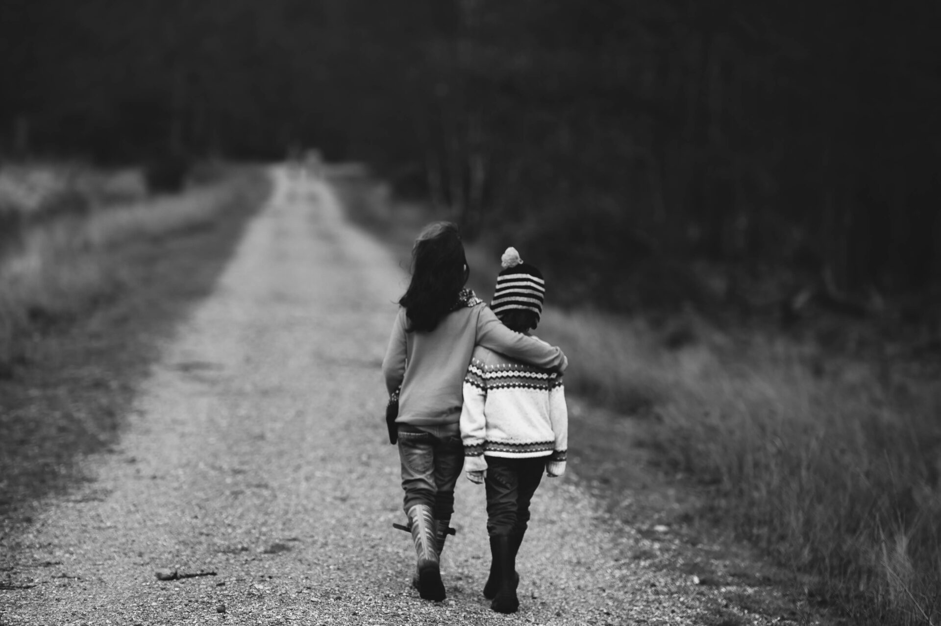 Young boys walk away down road with arms around each other in black and white photo