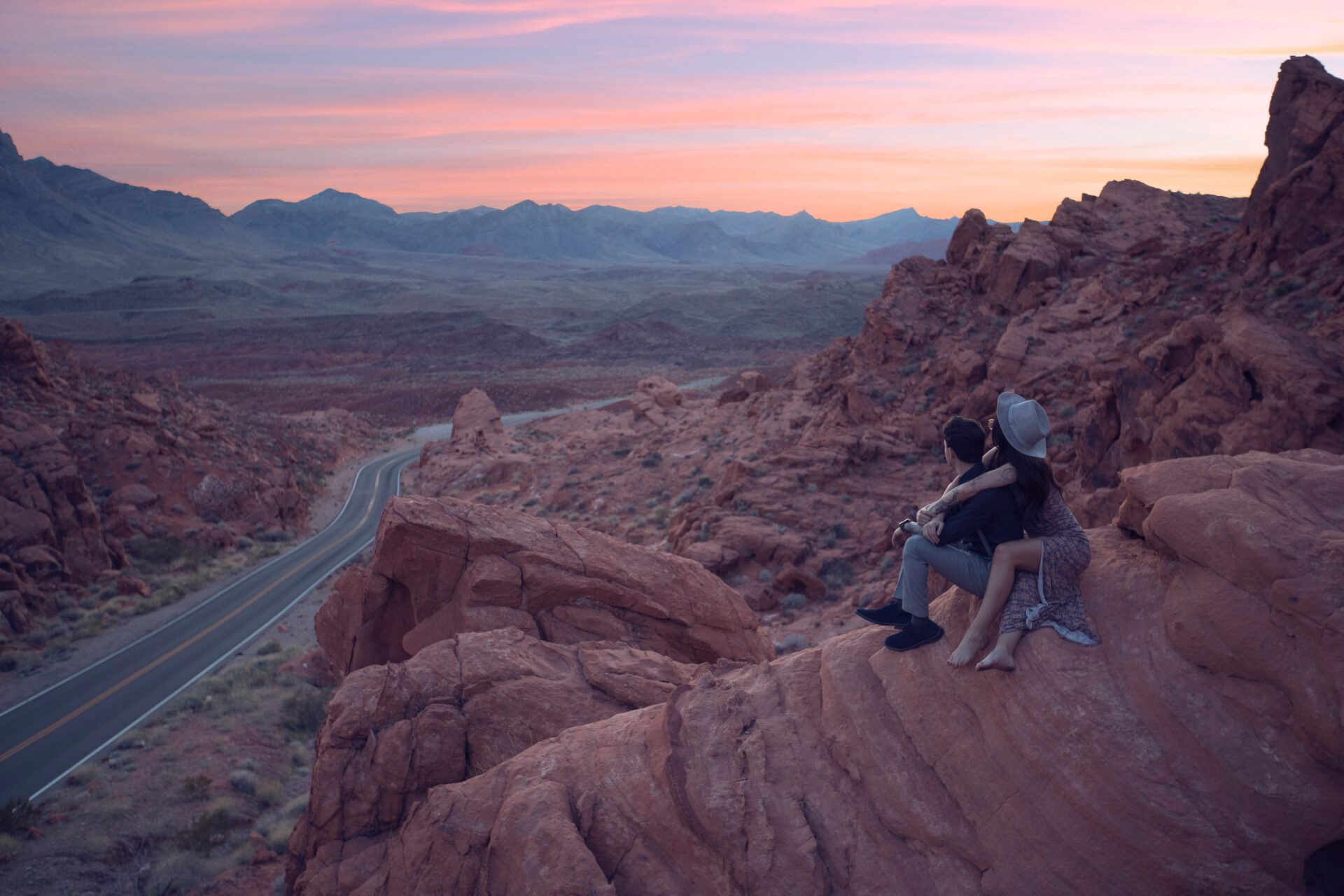 Couple watch sun set over sandstone landscape from high above road
