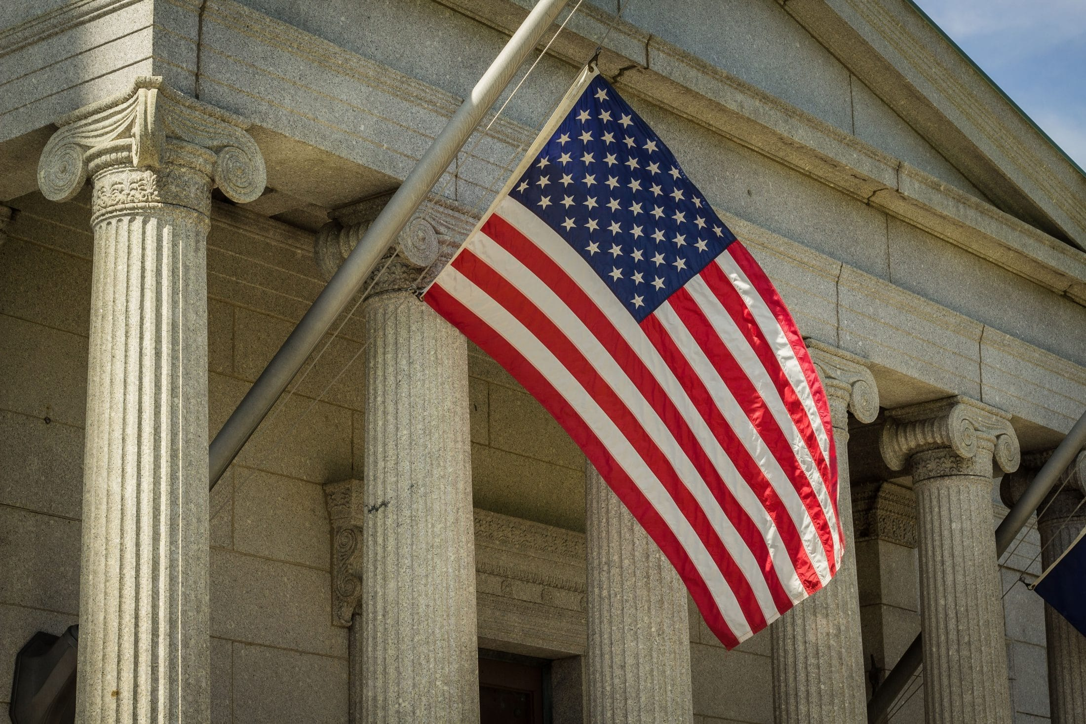 US flag hanging outside of government building
