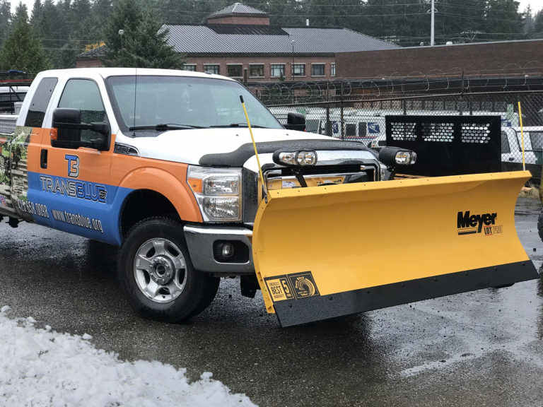 A Transblue truck with snow plow attached.