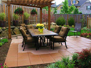 A photo of a backyard patio with seating and a pergola.