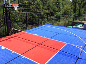 A photo of a blue and red combination tennis and basketball court.