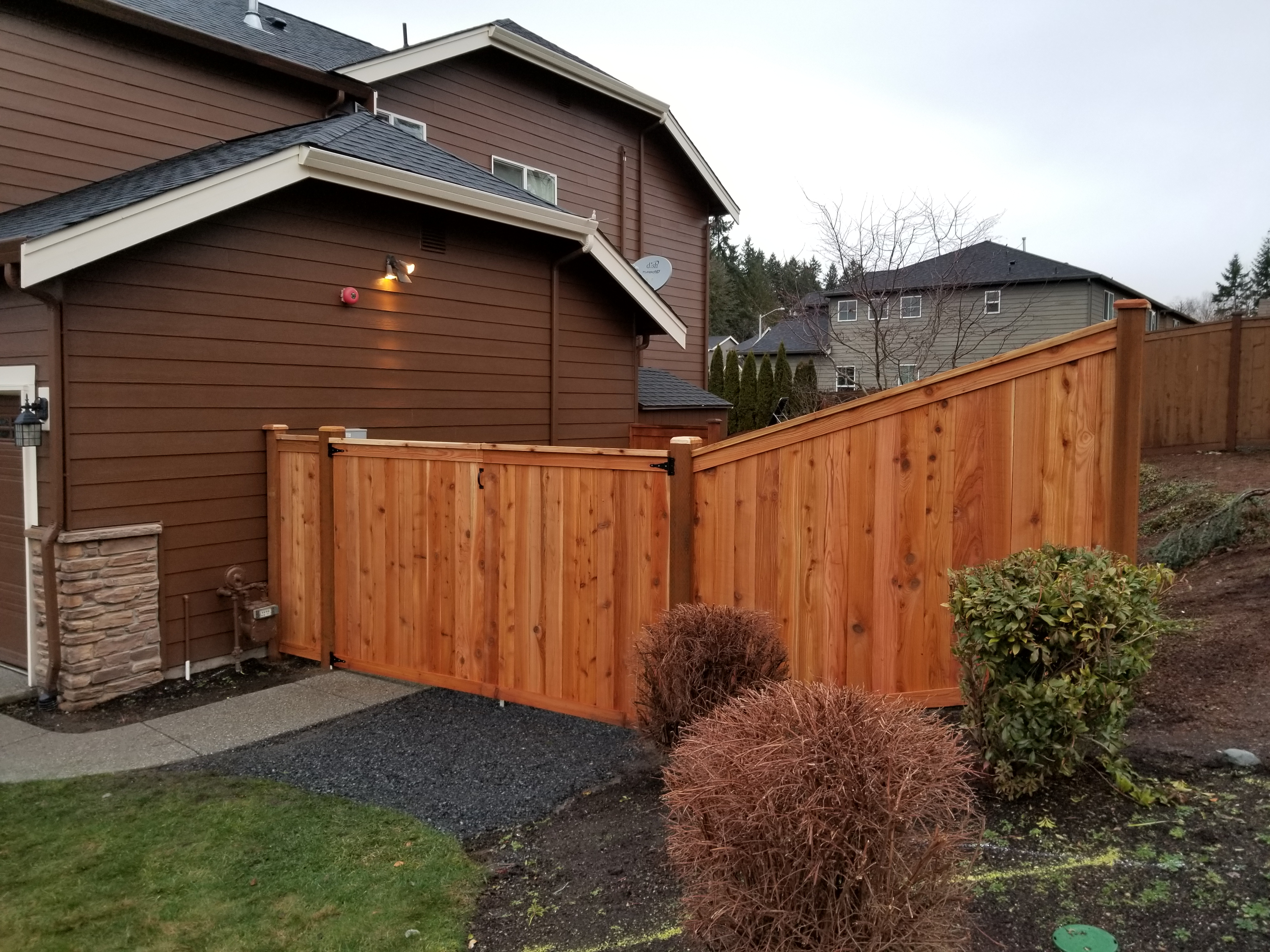 A wooden fence separating the front of a house from the back.