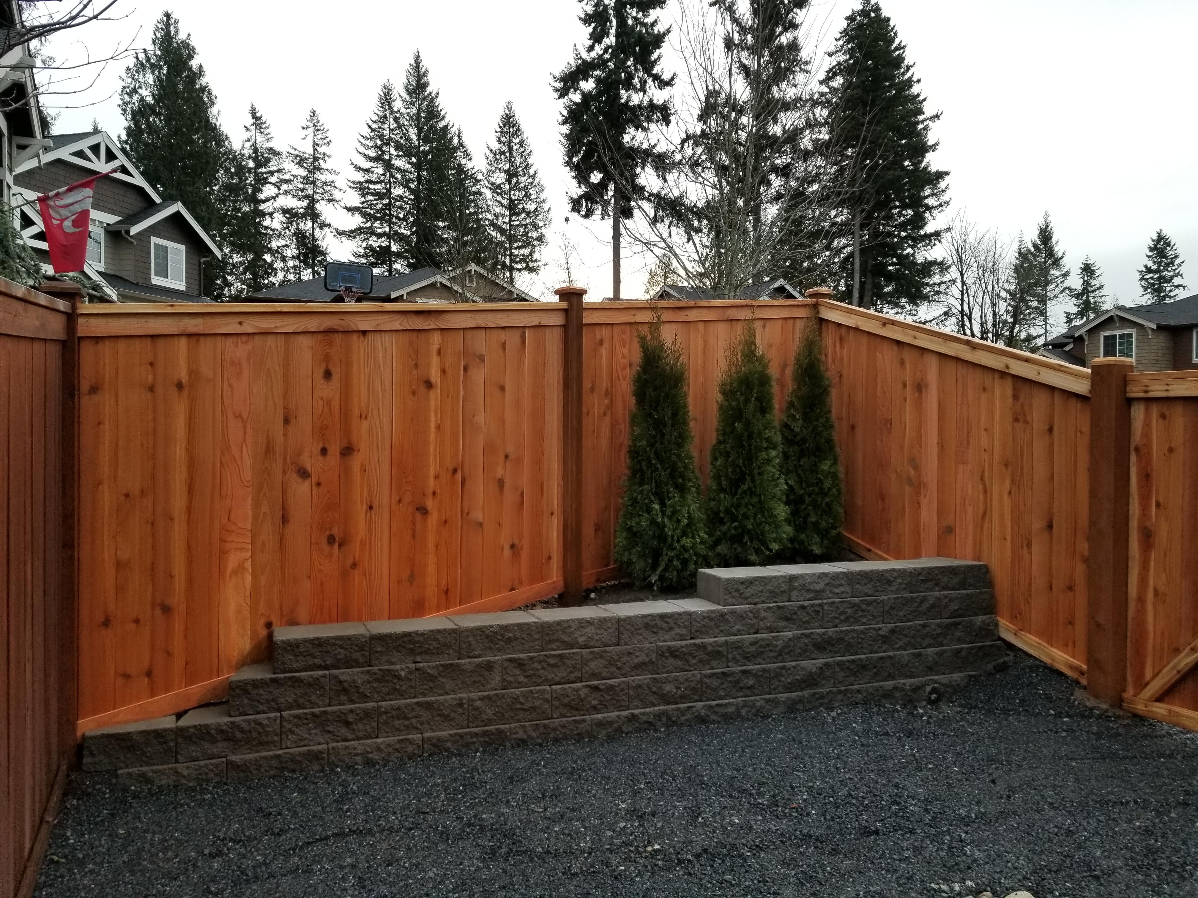 A wooden fence surrounding trees and a retaining wall.