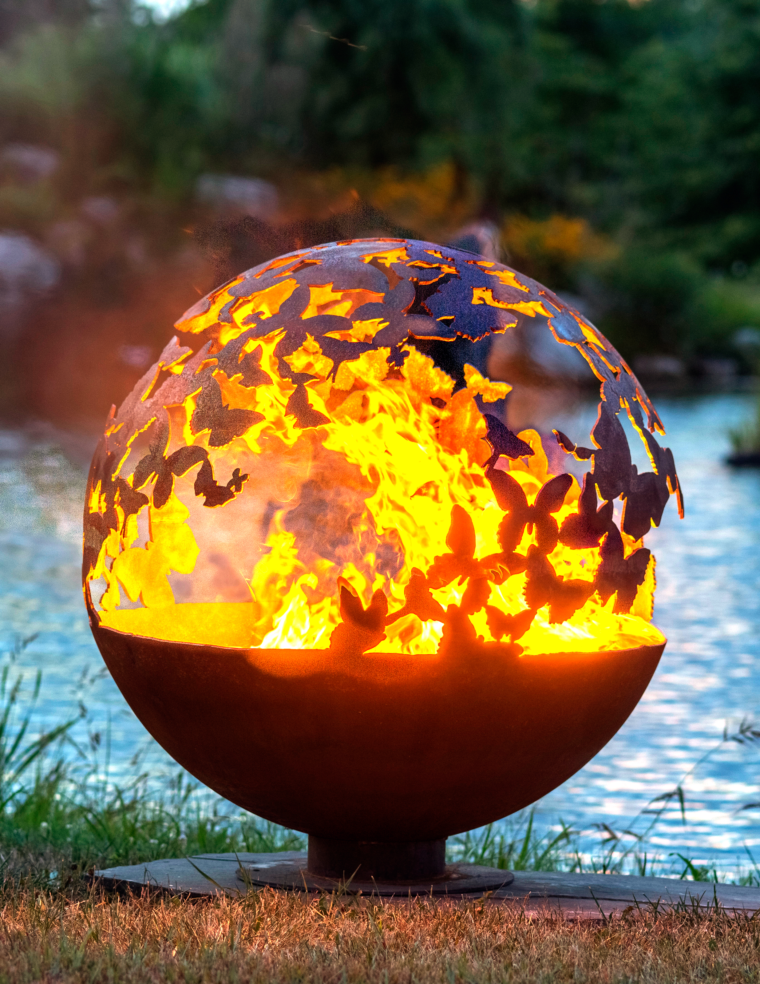 A photo of a spherical fire pit with a butterfly pattern.