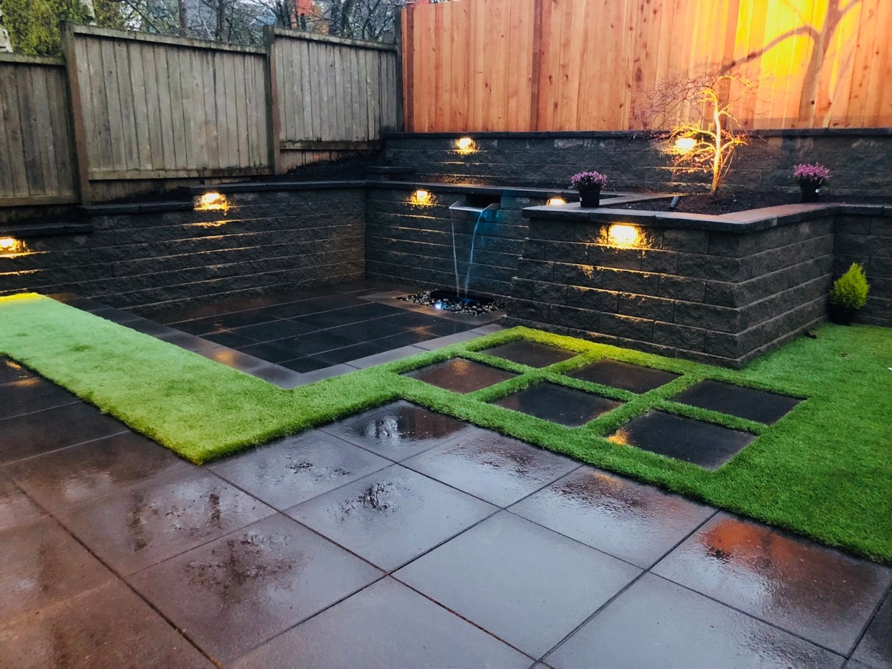 A backyard with retaining walls and a water feature.