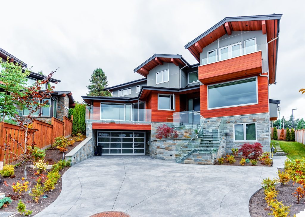 A photo of a paved driveway leading to a three-story home.