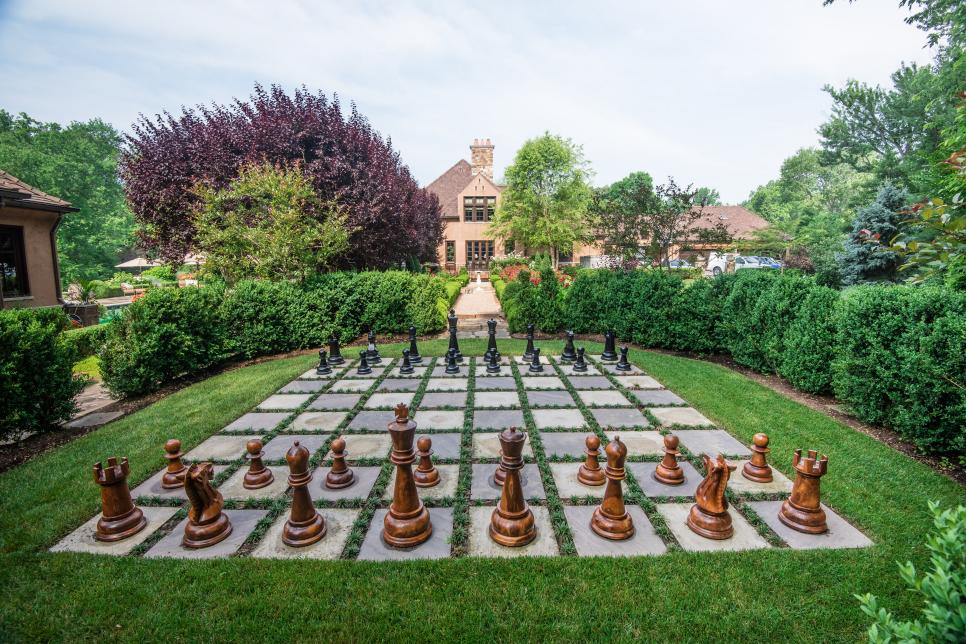 A photo of a large chess set in a backyard made of concrete on grass.