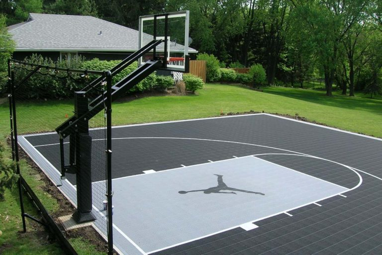 A photo of a backyard basketball court with a hoop.