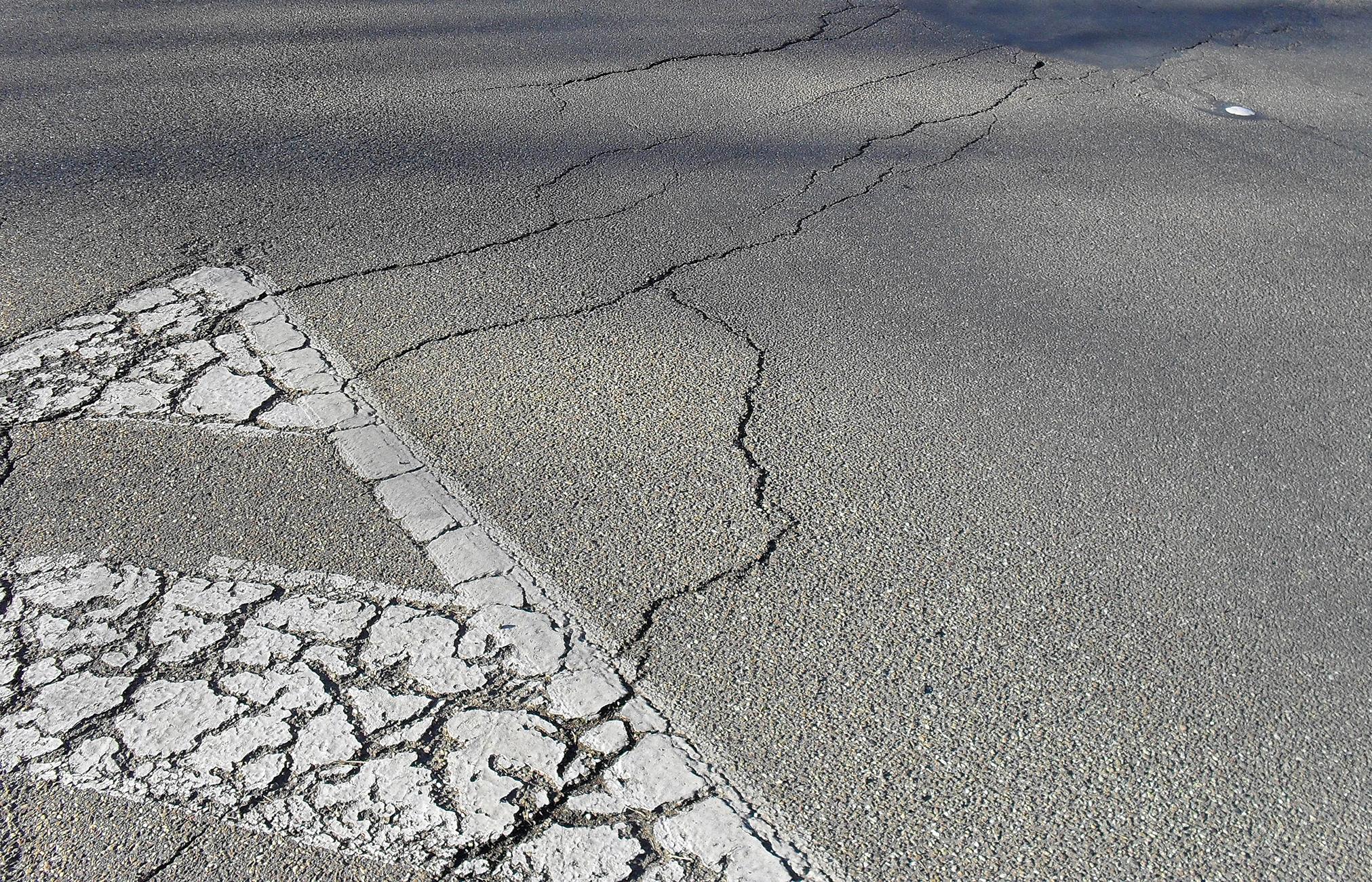 A photo of cracked asphalt.