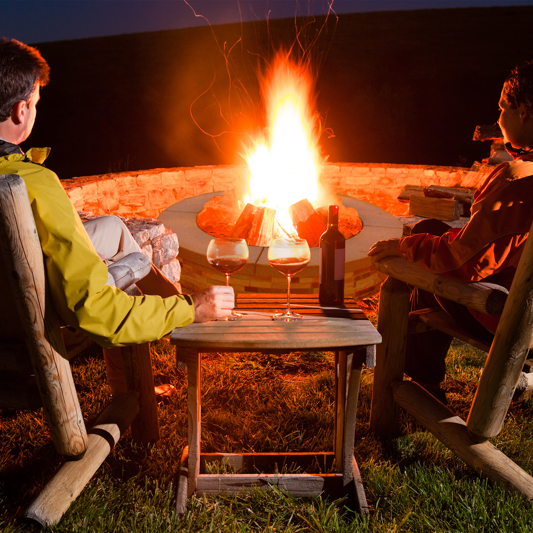 A photo of two people drinking wine by a fire pit.