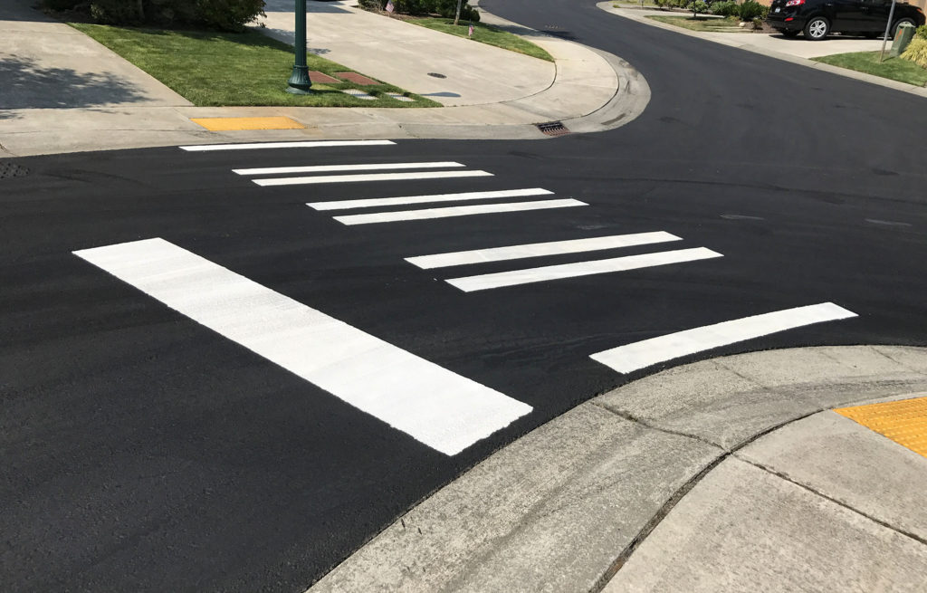 A photo of a paved street with a crosswalk.