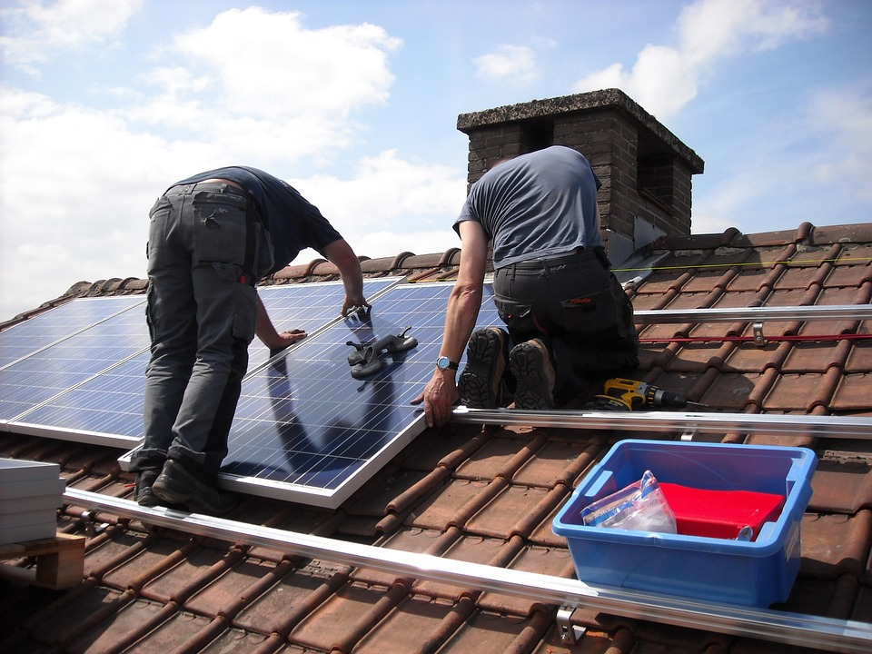 A photo of people installing solar panels on a roof.