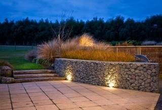 A patio leading to a rock retaining wall containing ornamental grasses.