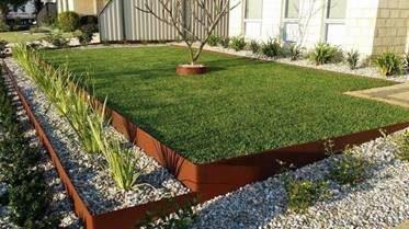 A photo of a landscaped grass area with a lower area containing ornamental grass.