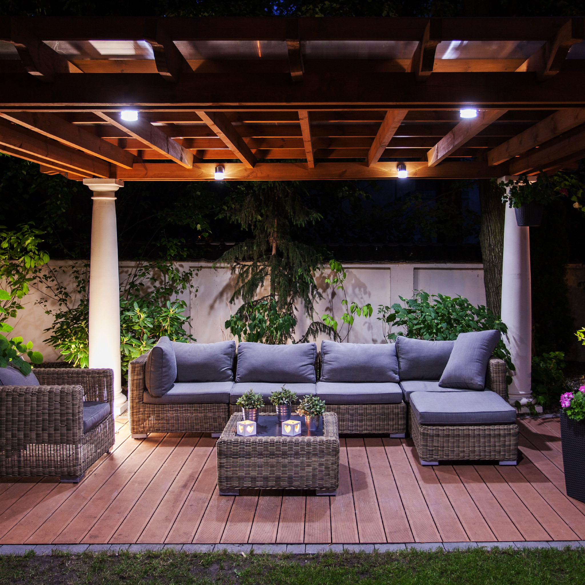 A backyard patio with seating and a table under a pergola.
