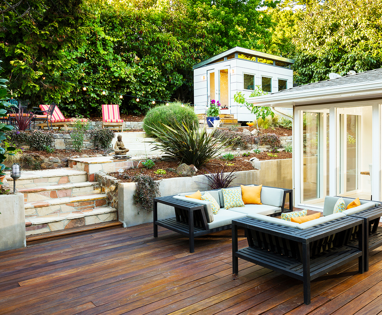 A photo of a backyard patio setup with benches and plants.