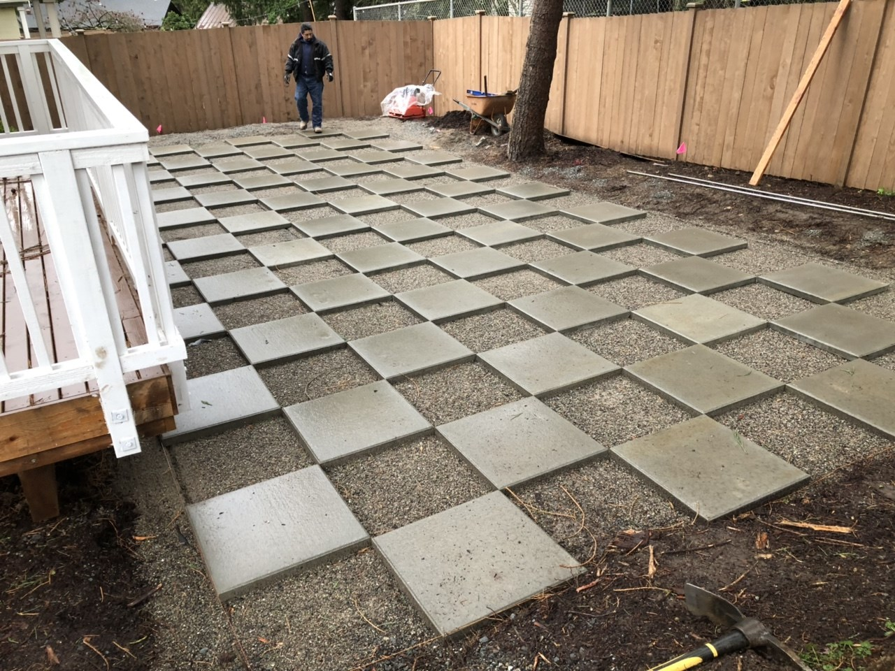 A photo of concrete blocks laid out in a backyard in preparation for a checkerboard lawn.