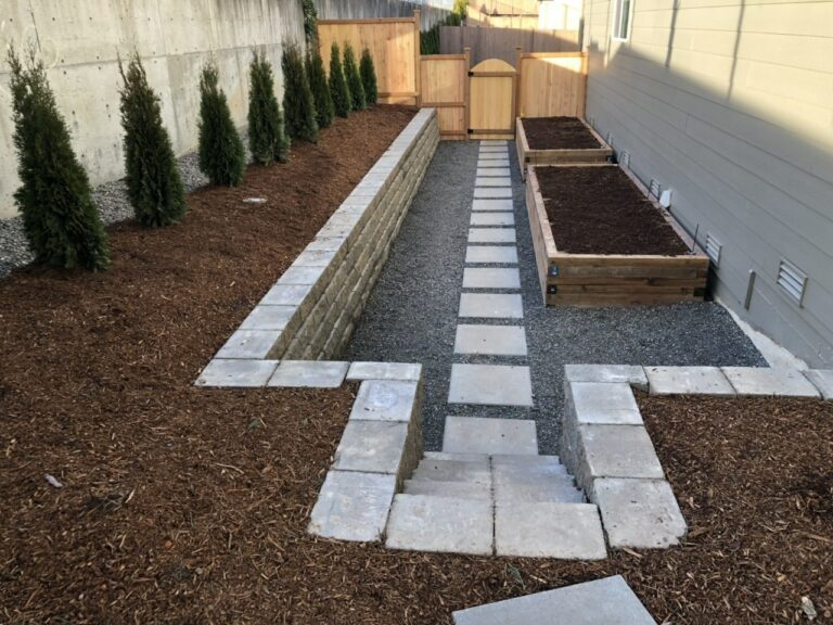 A photo of a backyard with stairs leading down to a recessed area with two raised garden beds.