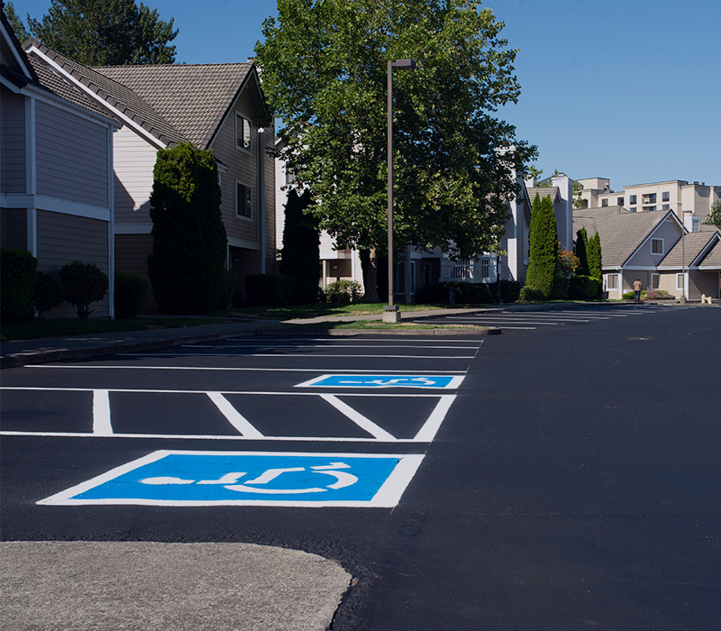 A paved parking lot outside an apartment complex.