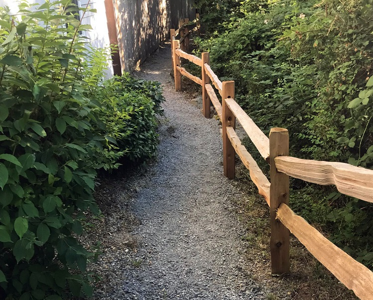A photo of a gravel walkway with greenery on one side and a wooden fence on the other.