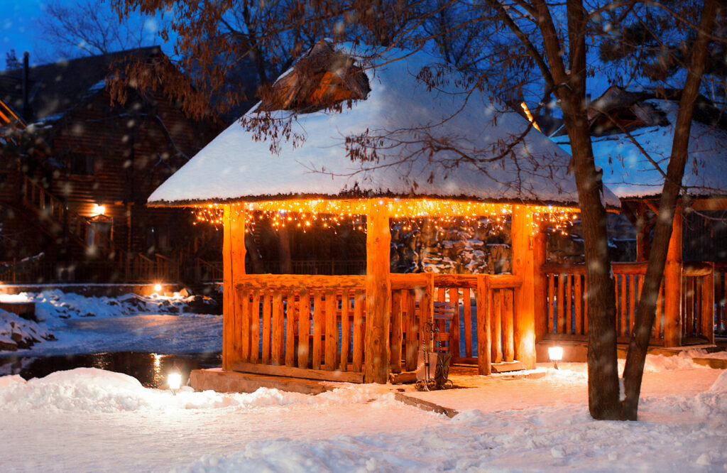 A photo of a gazebo in the snow with string lights.