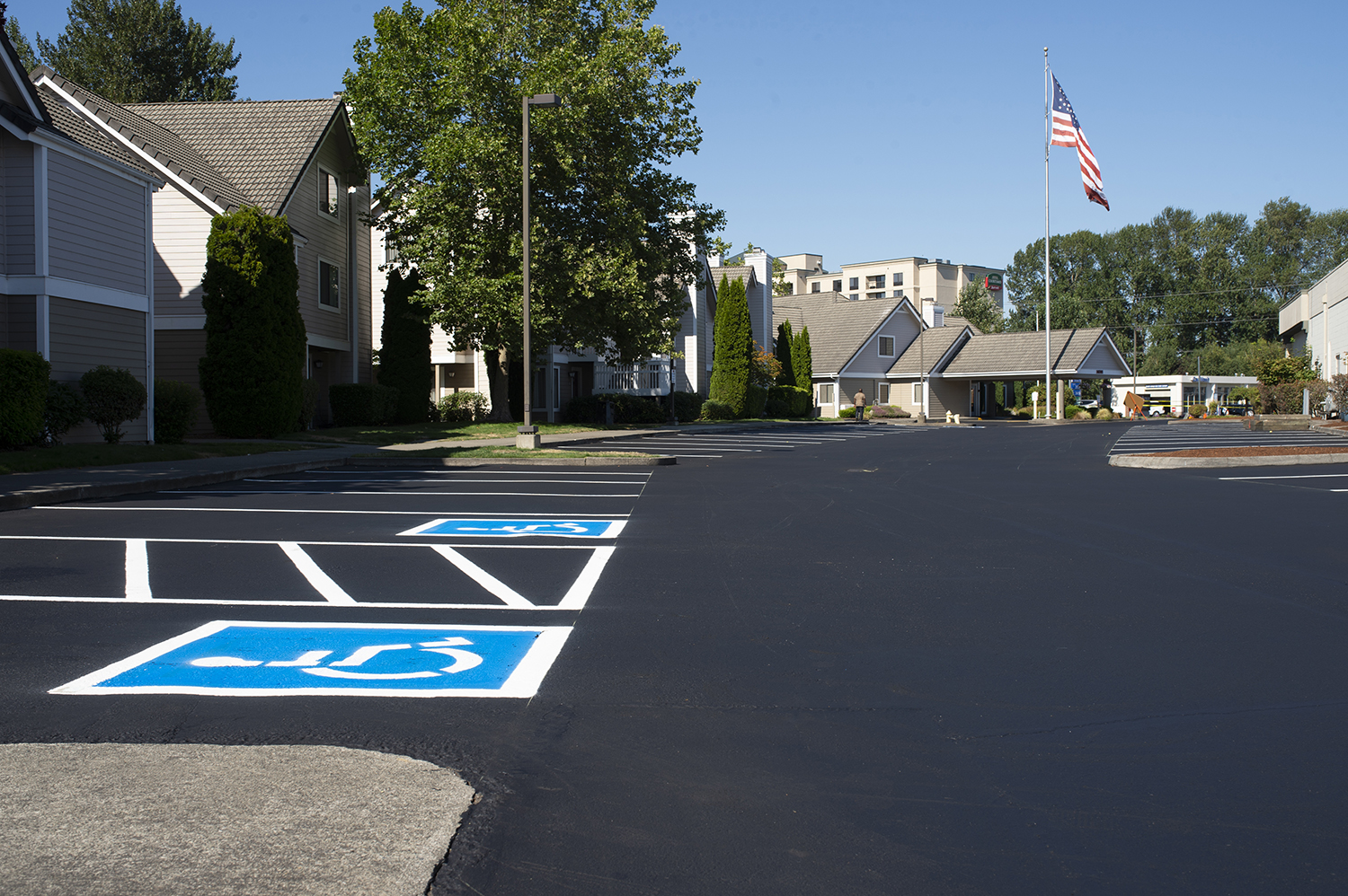 A freshly paved parking lot outside of a multifamily residence.