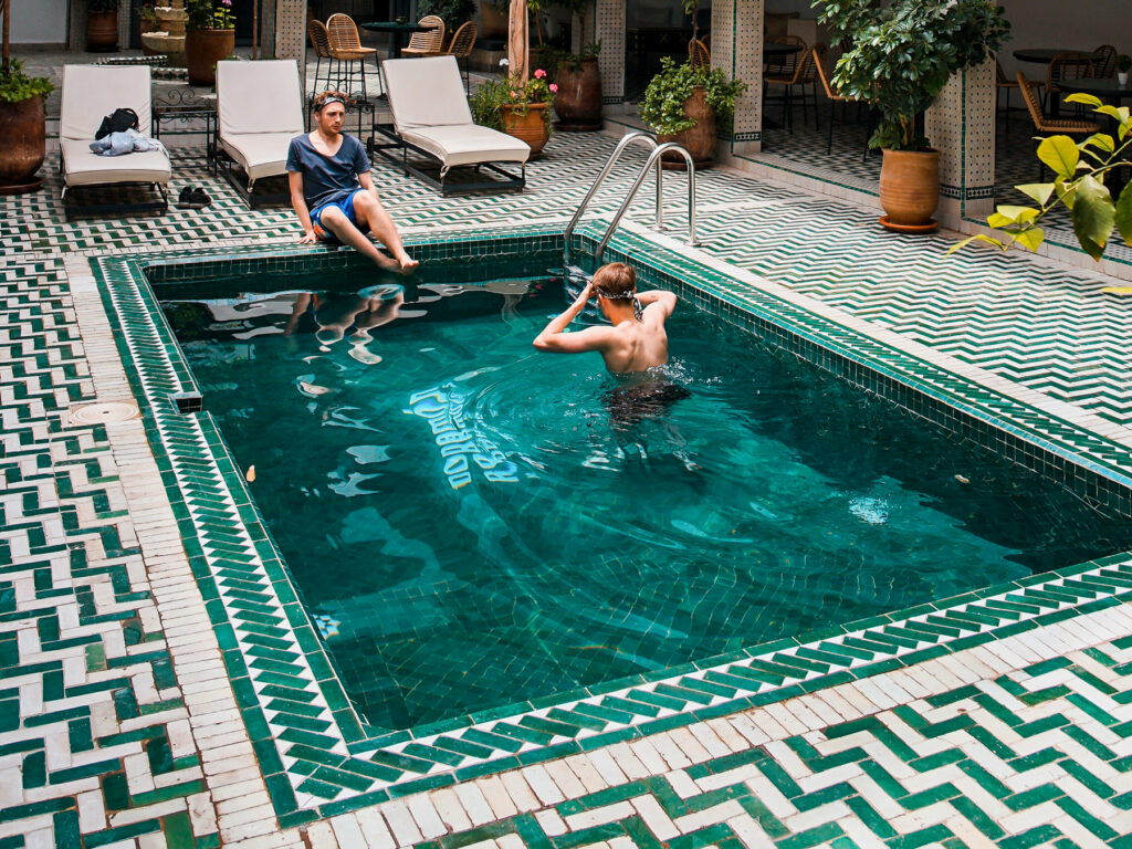 A photo of two people in a swimming pool surrounded by white and teal tiles.