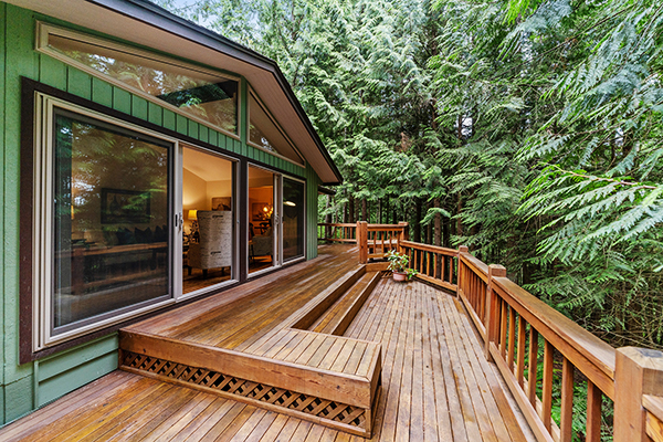 A photo of a wooden deck surrounded by trees.