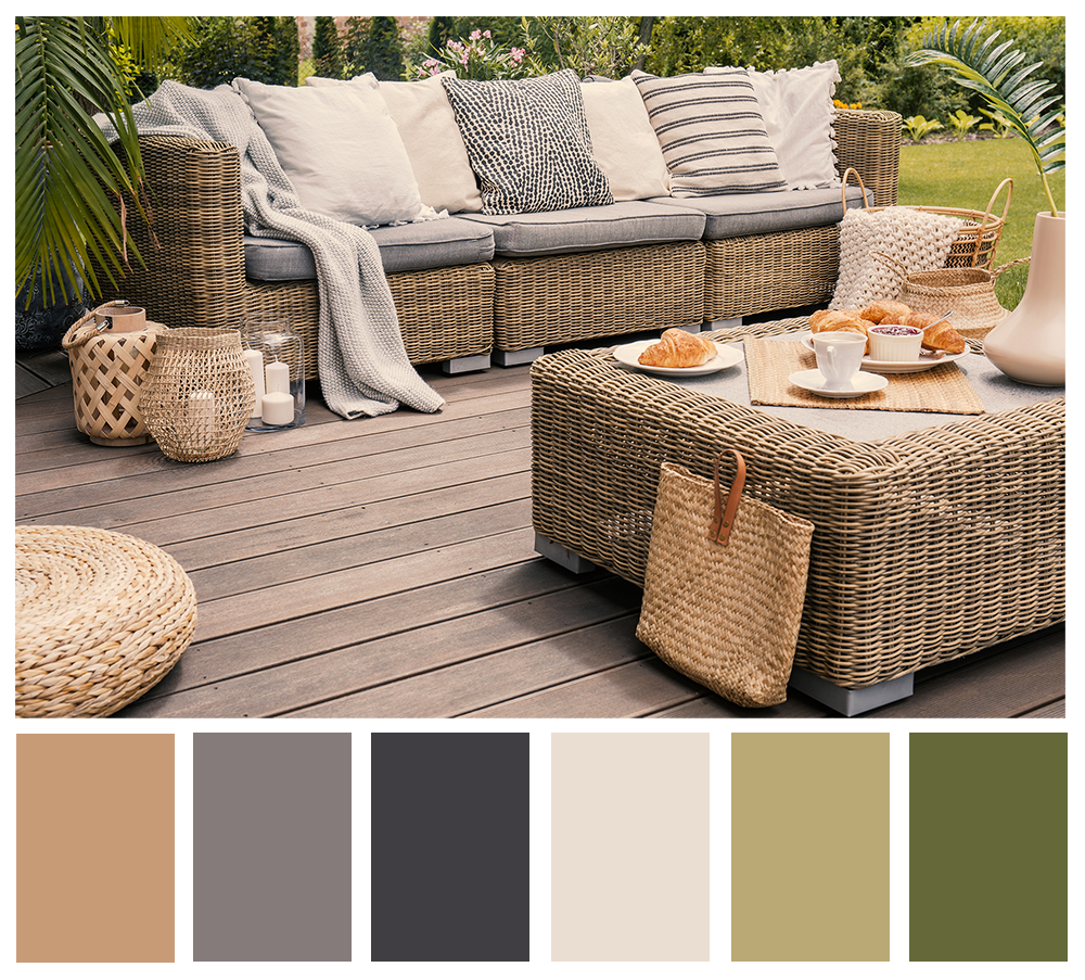 A hygge-style patio featuring rattan furniture with neutral-colored cushions and blankets.
