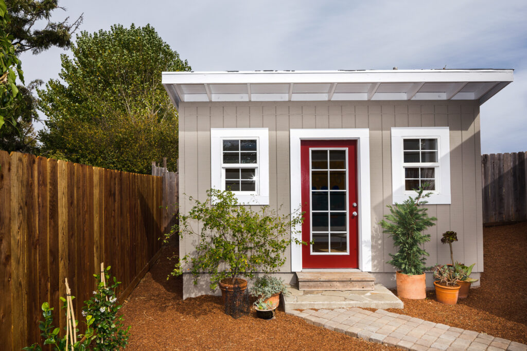 A gray outdoor shed with a red door.