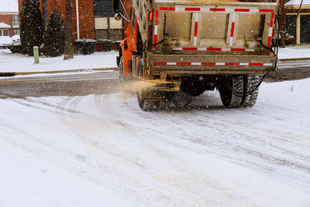 A de-icing truck spraying liquid de-icer on a street.