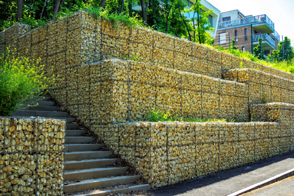 A gambion retaining wall, made of wire containers holding stones.