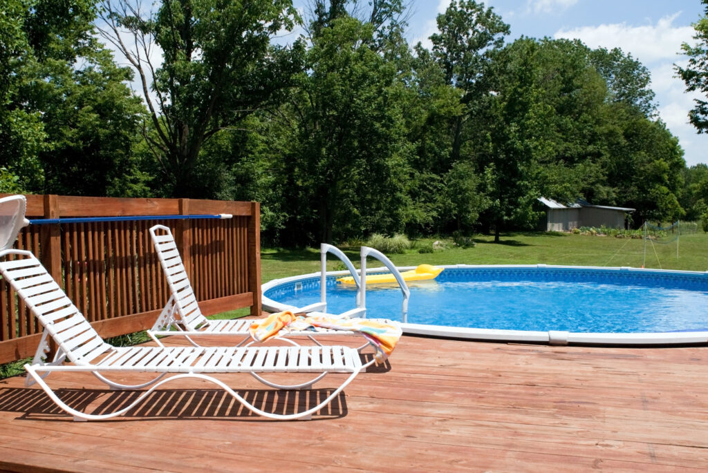 An above ground pool with a deck built around it.
