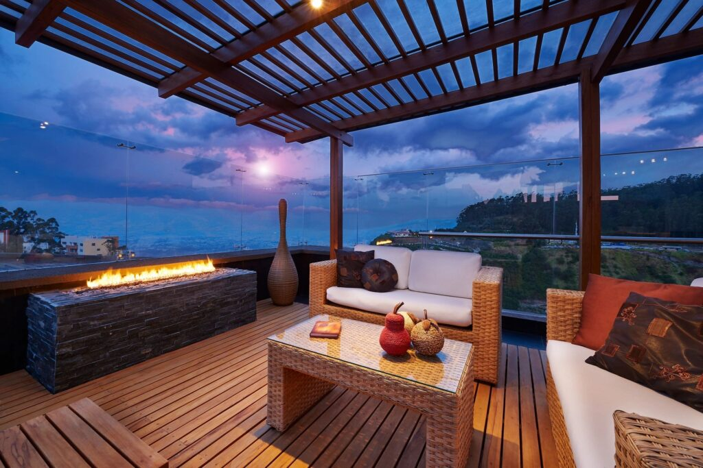 A photo of an outdoor patio with a pergola, furniture, and fire pit.