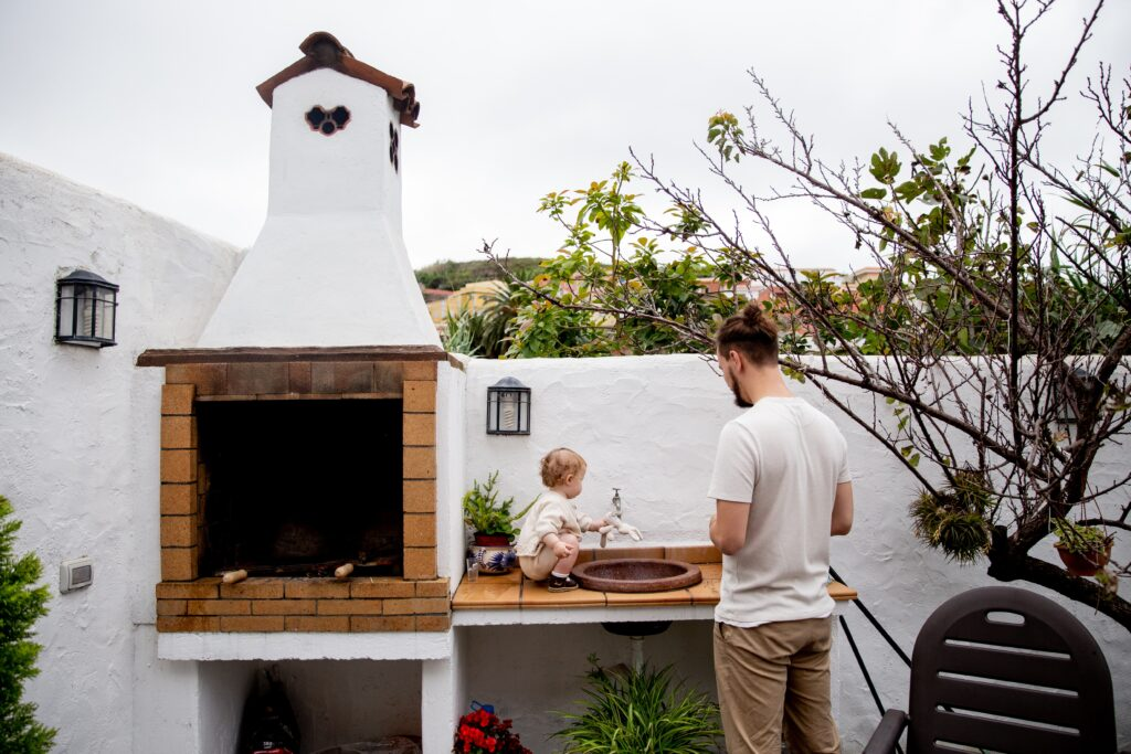 A photo of a man and child at an outdoor kitchen.