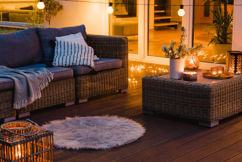 patio with fairy lights a white rug and a couch with white pillows