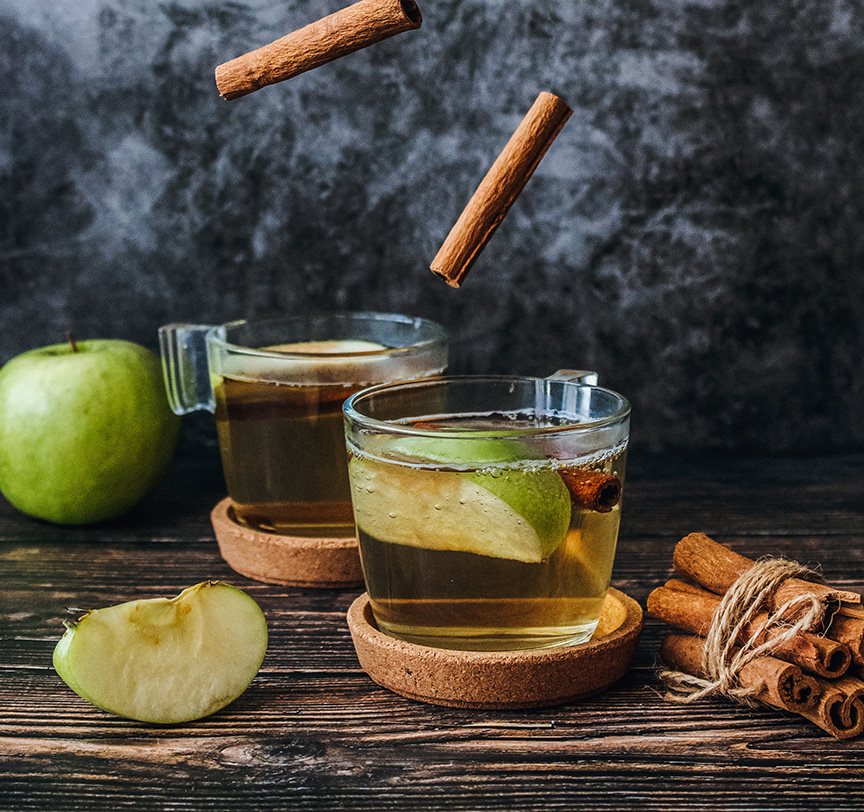 granny smith apples and cinnamon sticks falling into a clear drink