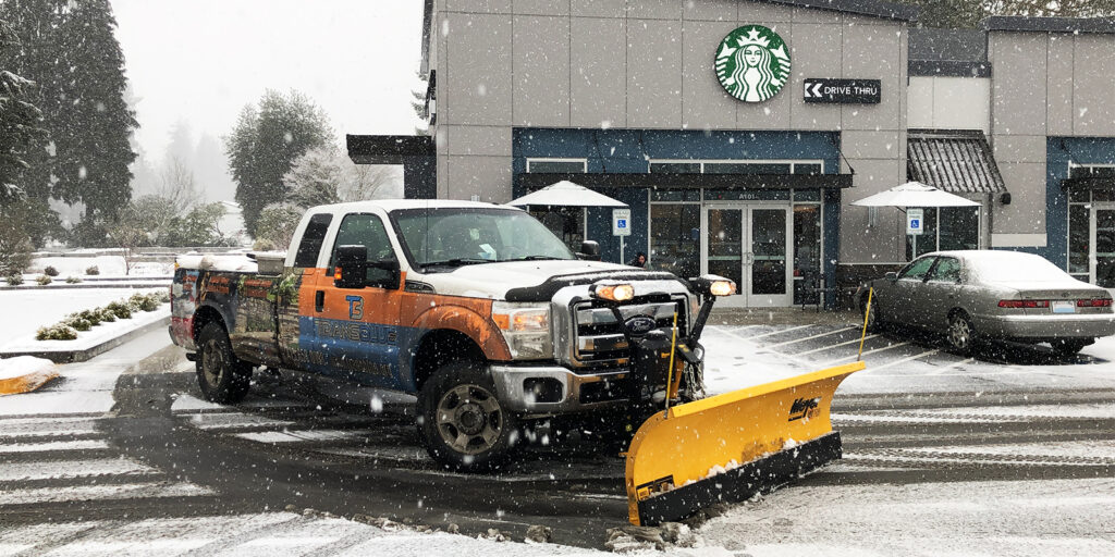 pickup truck with orange snow plow attached plowing a starbucks parking lot