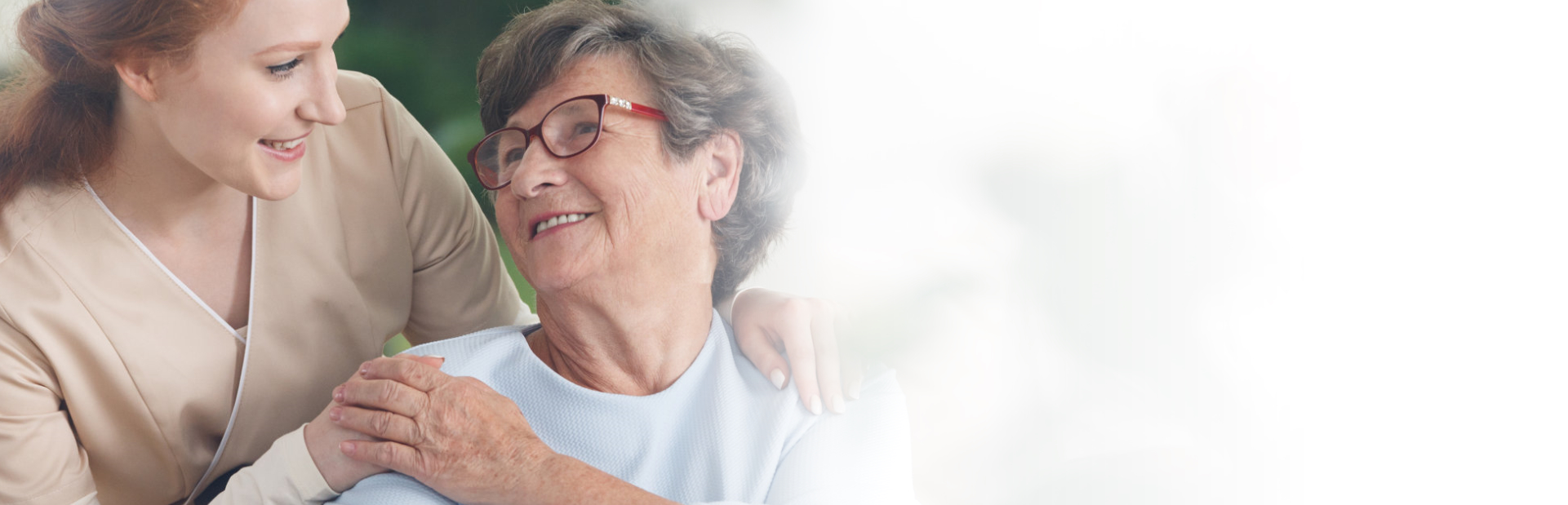 caregiver and senior woman smiling with each other