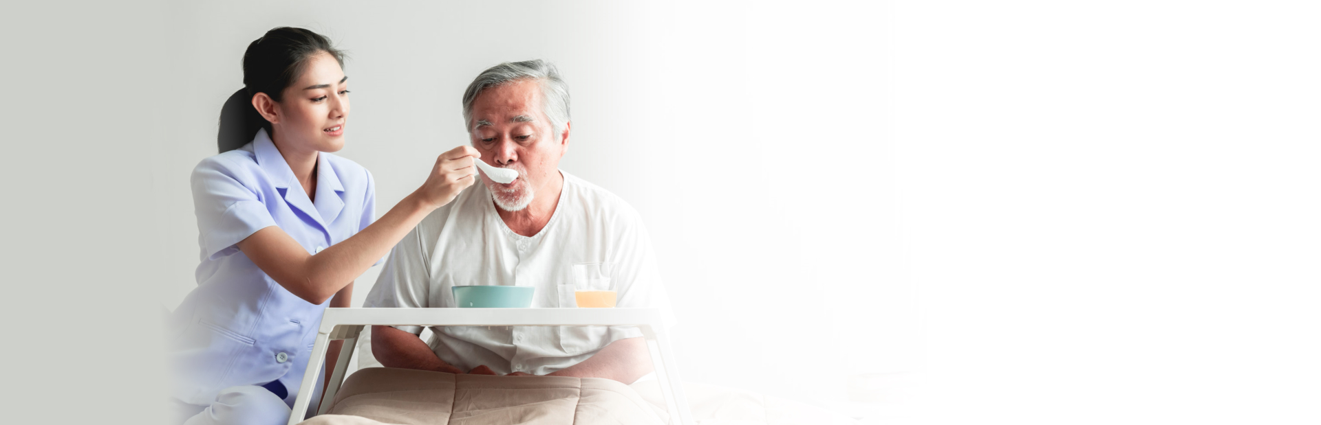 caregiver assisting senior man in eating