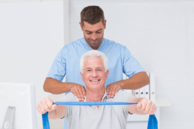 Male physiotherapist assisting senior patient in exercising with resistance band at clinic