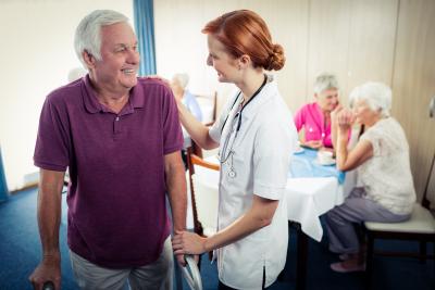 nurse assisting an elder man in using a walker
