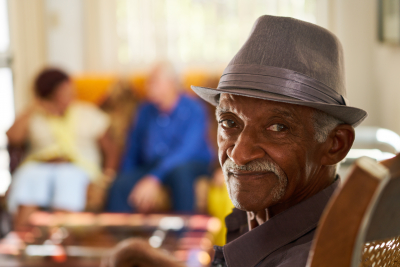 elderly man looking in retirement home, with group of friends in background