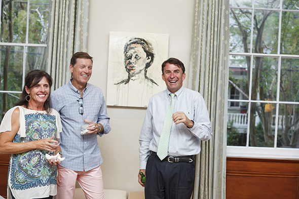 Painting by Timmy Pakron hangs behind Mike and guests