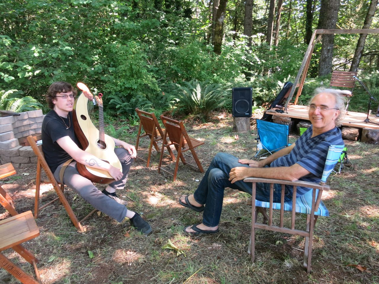 John gives a private lesson to Adrian in the woods with the harp guitar.
