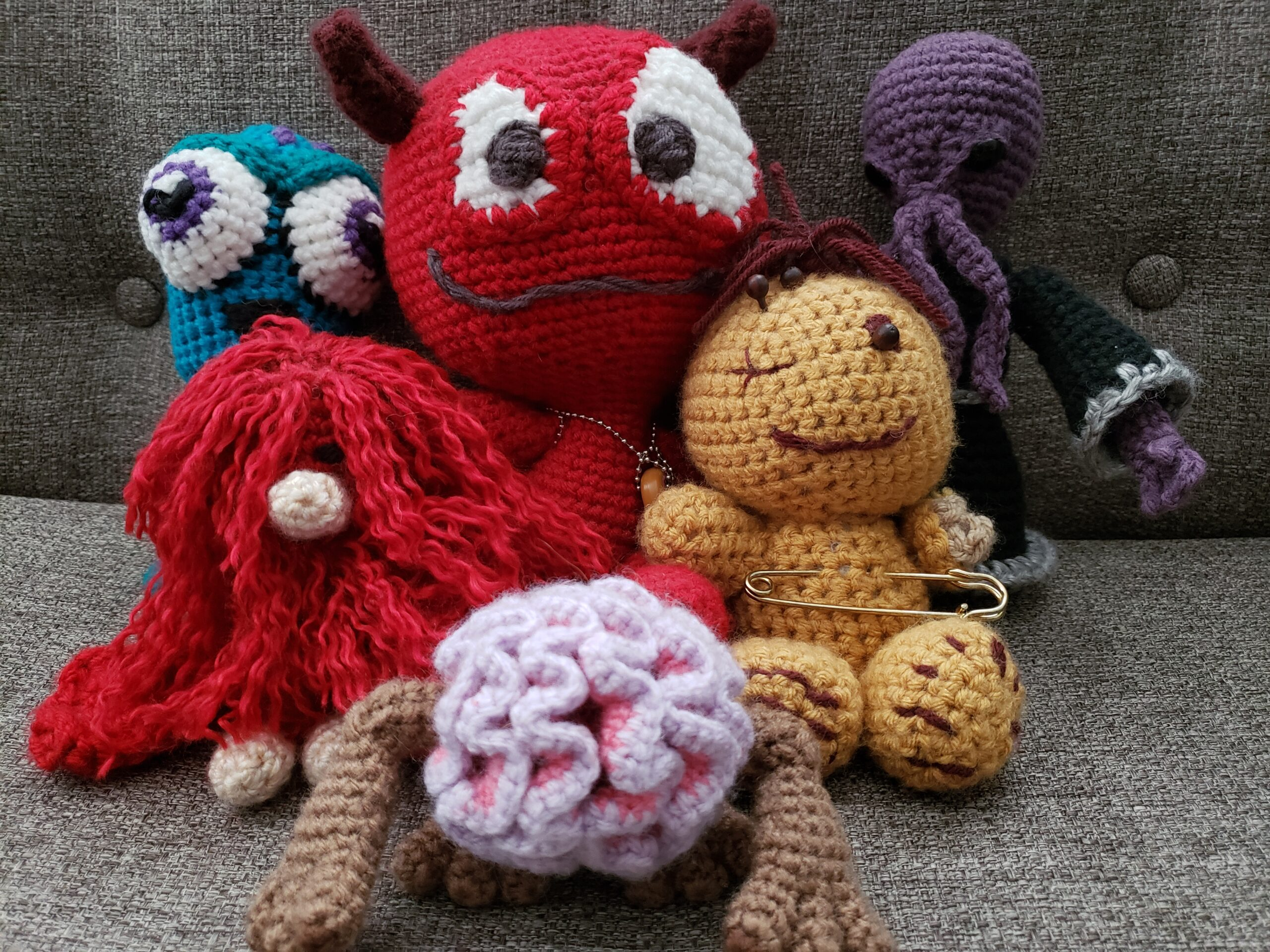 Several different crocheted amigurumi: a squid, a red yeti, a demon named Stinky, an ilithid, a voodoo doll, and an intelligence devourer